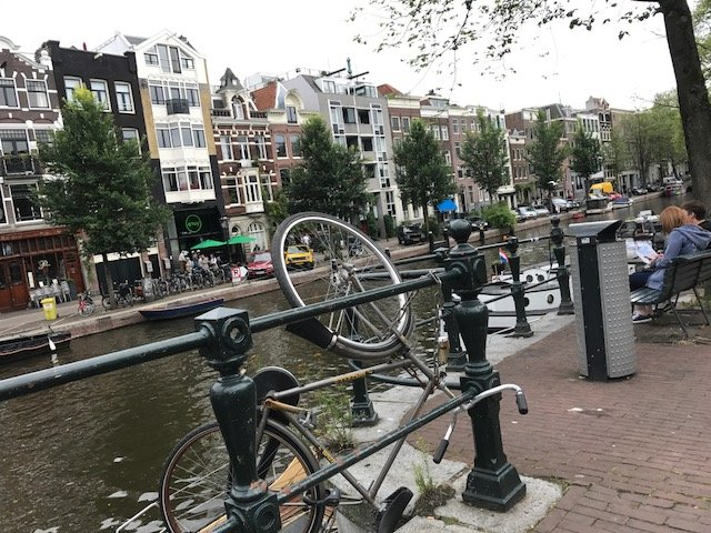 Bike hanging on the railing of the canal - not a rare catch - Bikes Amsterdam