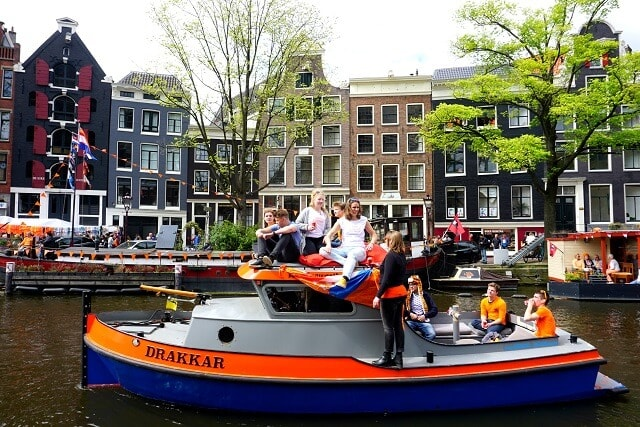People on orange boat during Kingsday